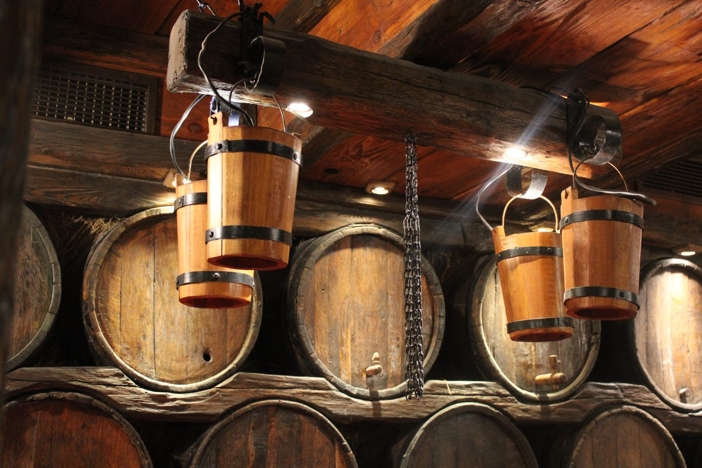 traditional bulgarian food in sofia: inside a restaurant where wooden buckets are hanging from the ceiling and barrels are on the wall