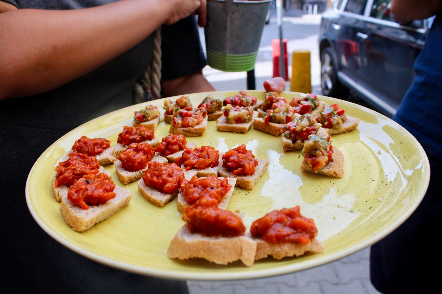 traditional bulgarian food in sofia: a plate topped with bitesize portions of bread topped with a bright red relish