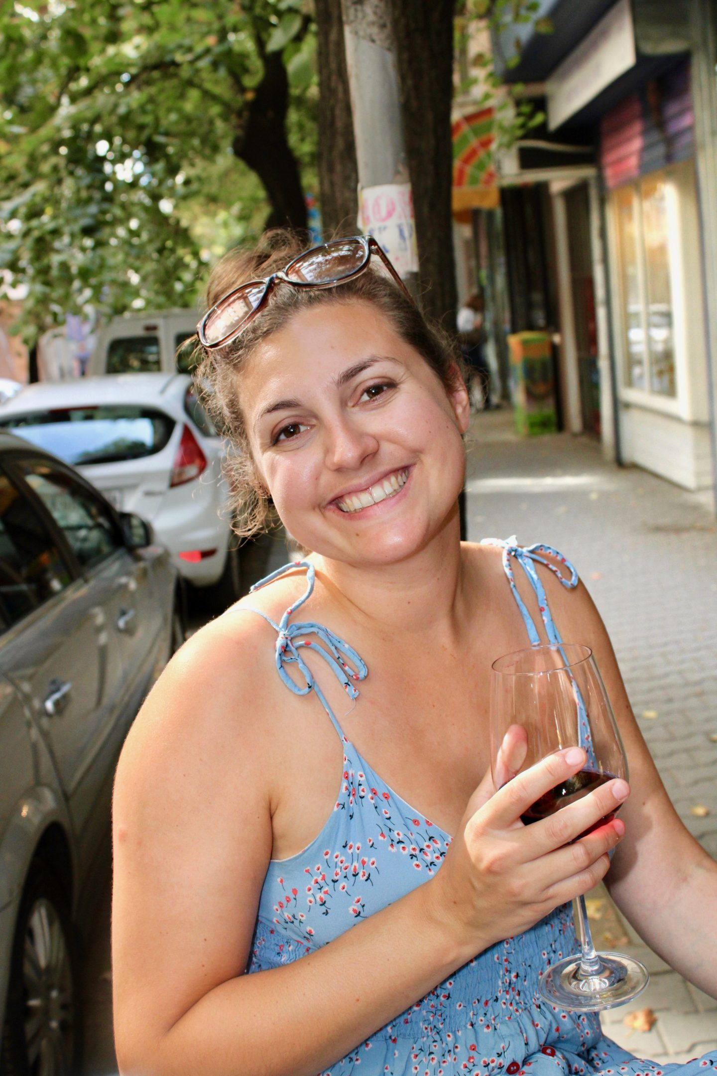 traditional bulgarian food in sofia: nell holding a glass of red wine and looking slightly tipsy