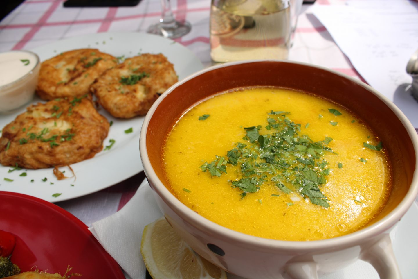 traditional bulgarian food in sofia: A bowl of yellow chicken soup, with potato pancakes just out of focus in the background