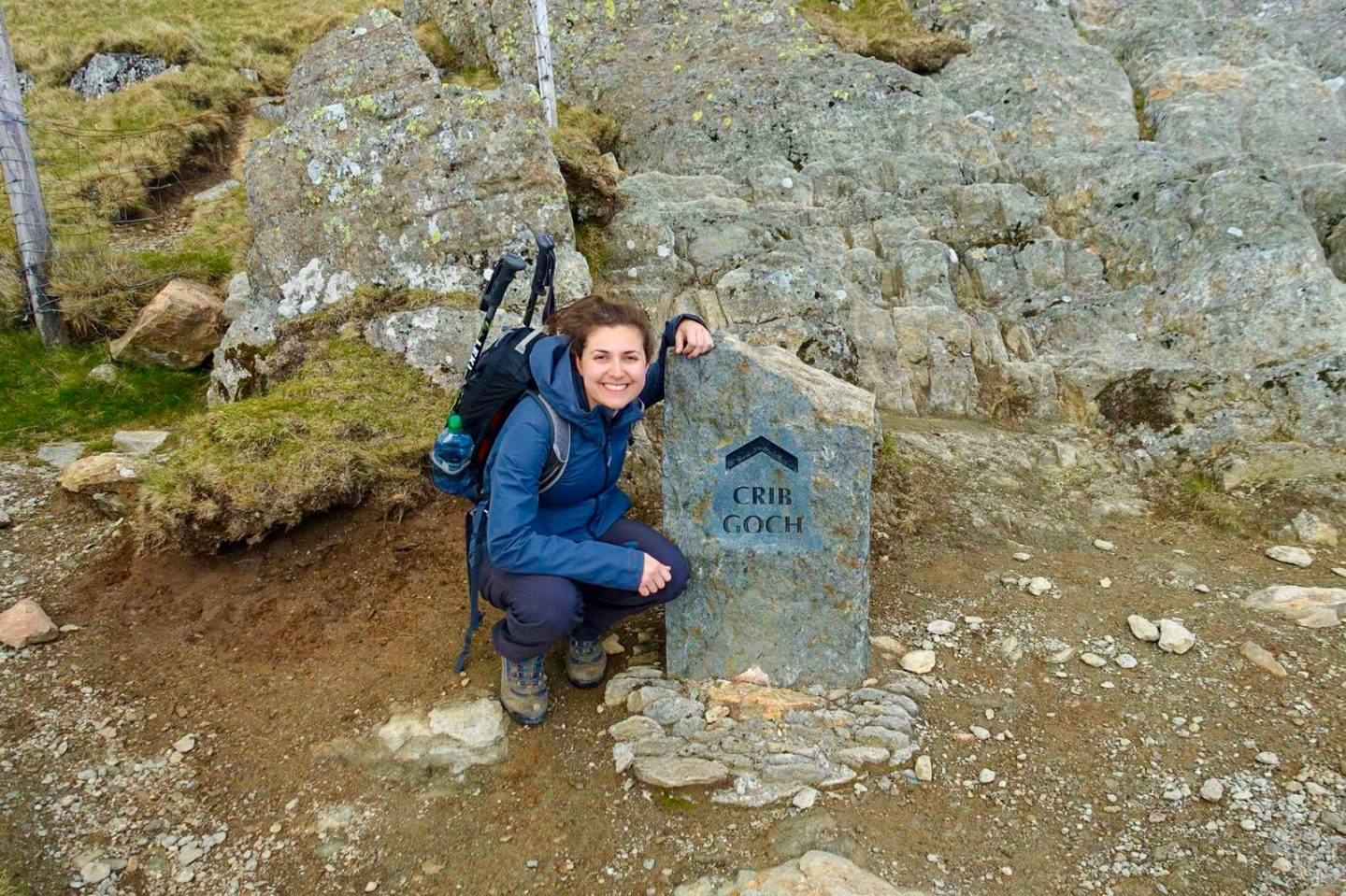 crib goch route up snowdon - Nell crouched next to a stone sign and smiling at the camera