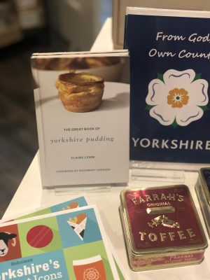 shopping in Leeds corn exchange: a display of Yorkshire gifts including a book about Yorkshire puddings