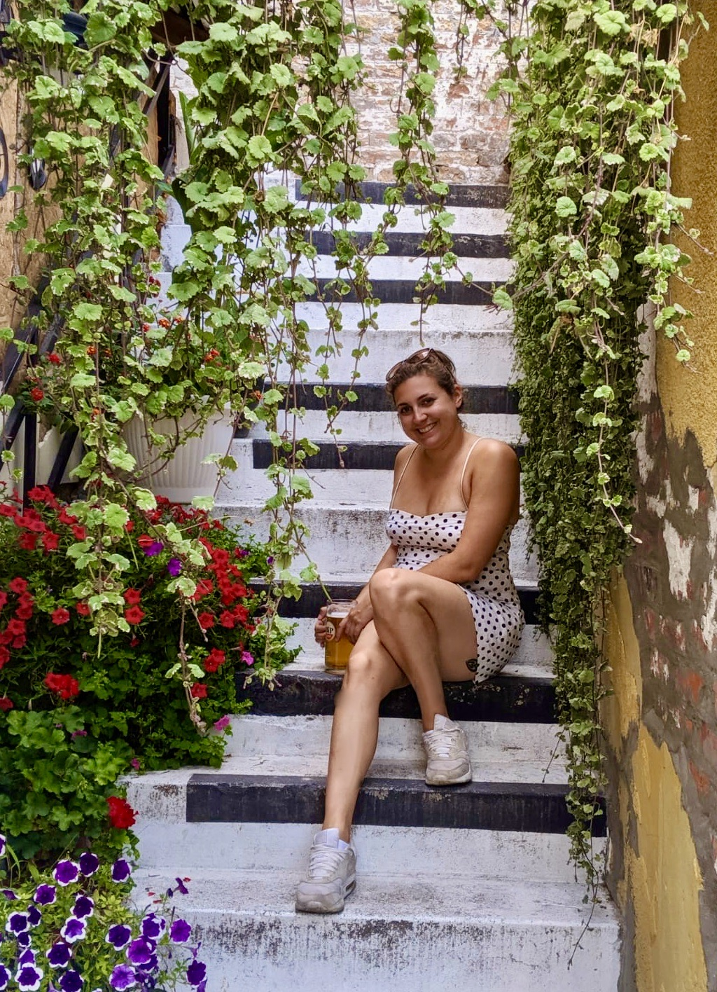 Visit Belgrade - Nell sat on some steps surrounded by plants and flowers, drinking a beer at a bar in Belgrade, Serbia